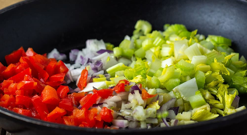 Onion, celery, bell pepper chopped for vegan dirty rice in black skillet