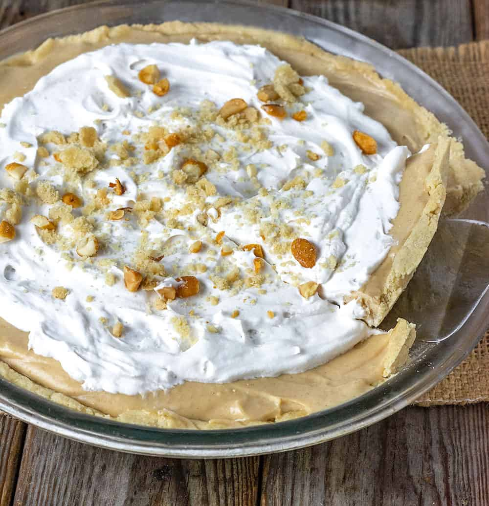 Whole peanut butter pie, made with vegan cream cheese, coconut cream, peanut butter, maple syrup. garnished with coconut whipped cream