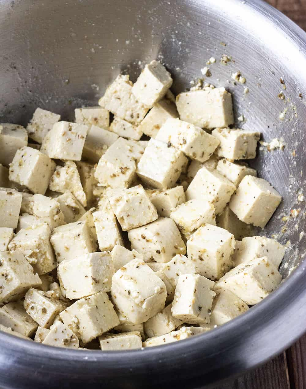 seasoned tofu cubes for vegan feta cheese in a silver bowl
