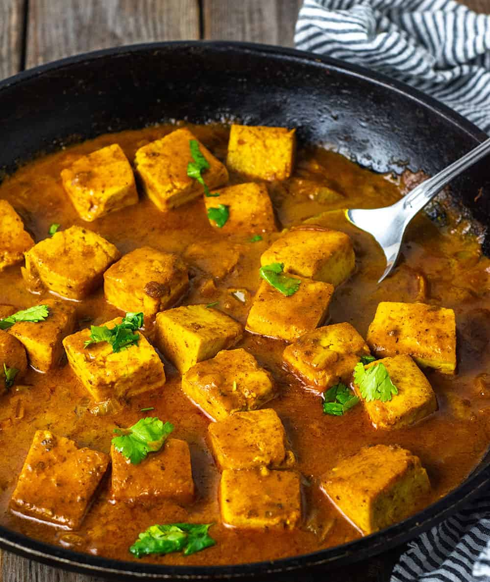 Tofu tikka masala straight on view in a black skillet with lots of curry sauce, garnished with cilantro leaves on a wooden background with a silver spoon