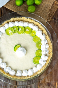 Vegan Key lime pie made with cashews, coconut cream, maple syrup in a graham cracker crust, garnished with coconut whipped cream, key lime pie slices on a wooden background with key limes on a burlap napkin, overlay image