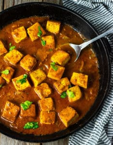 Tofu tikka masala cubes in a creamy aromatic tomato sauce in a black skillet with a silver spoon on a wooden background with a black and white stripe napkin