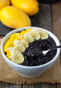 Easy black rice pudding, cooked with coconut milk, cinnamon, nutmeg and vanilla and sweetened with coconut sugar in a white bowl, topped with slices of banana, mango and coconut flakes on a wooden background. 3 mangoes in the background on a black slate