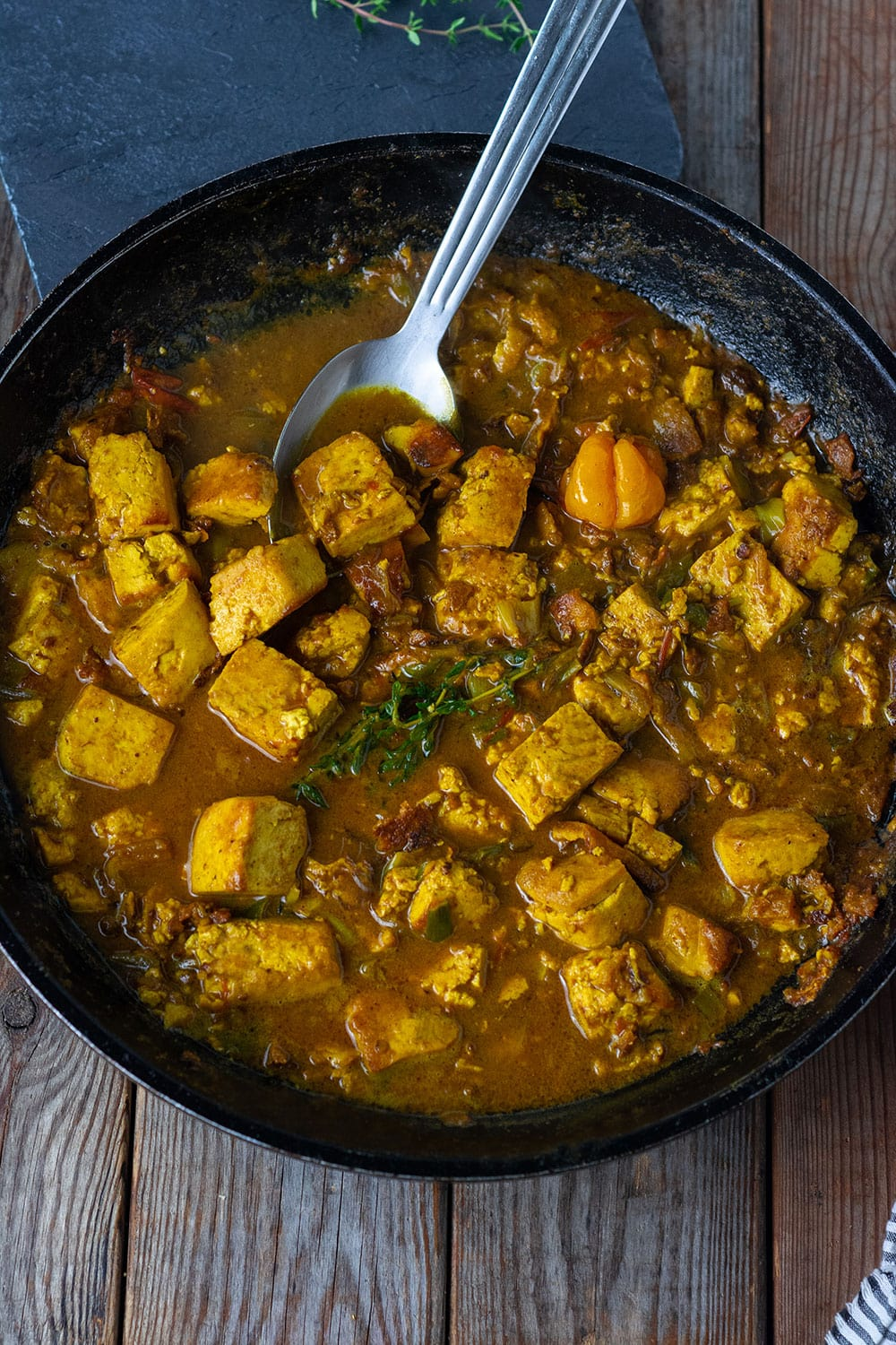 easy Tofu curry made with caribbean curry cooked in a seasoned coconut milk sauce with exotic herbs and spices, thyme, Scotch bonnet pepper in a black skillet with a silver spoon.