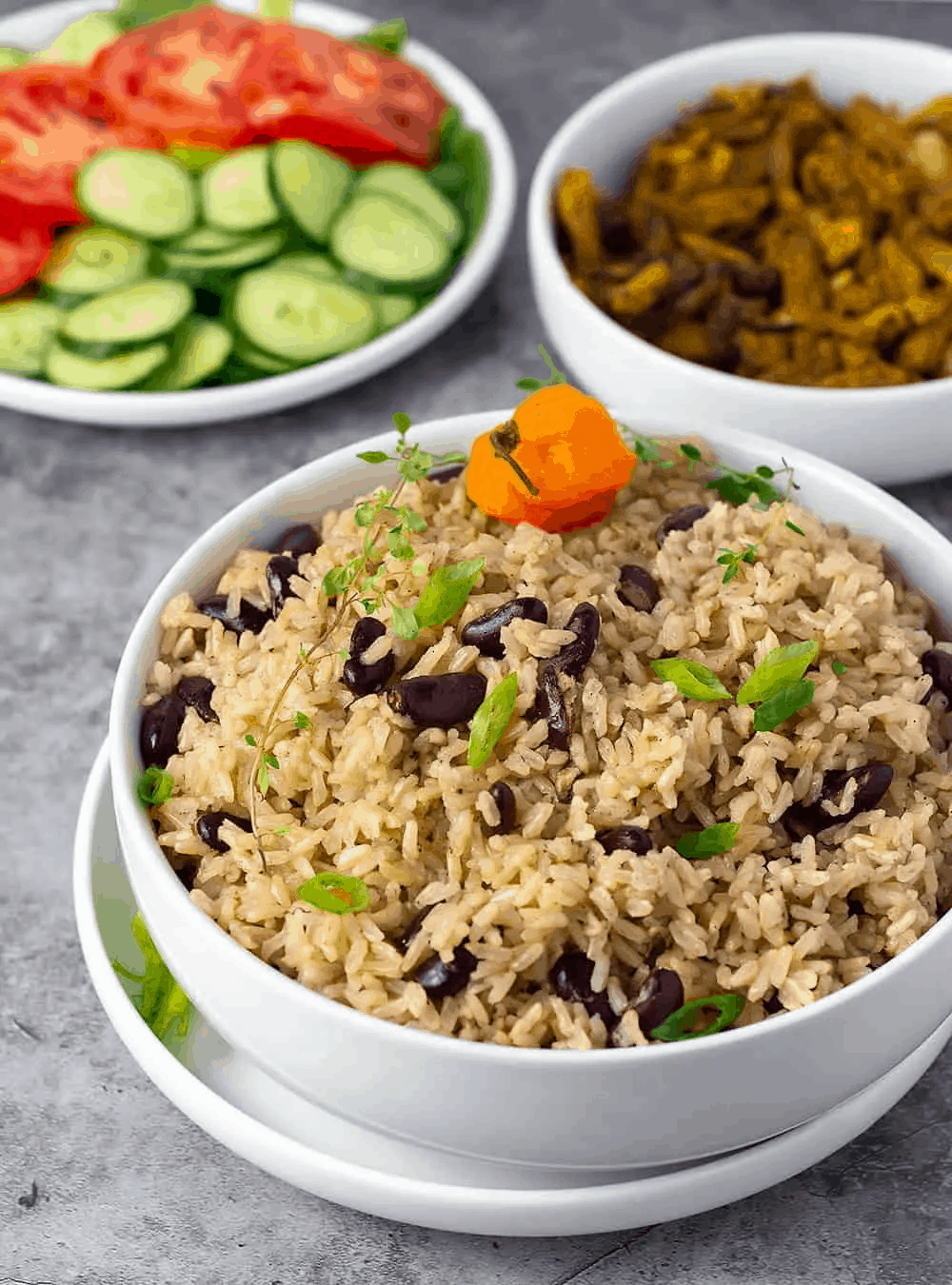 Jamaican rice and peas in a white bowl on a grey background with salad on a plate in the background