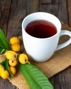 loquat tea from fresh loquat leaves in a white cup , the tea looks red, on a burlap napkin on a wooden background with loquat fruit and leaves to the side