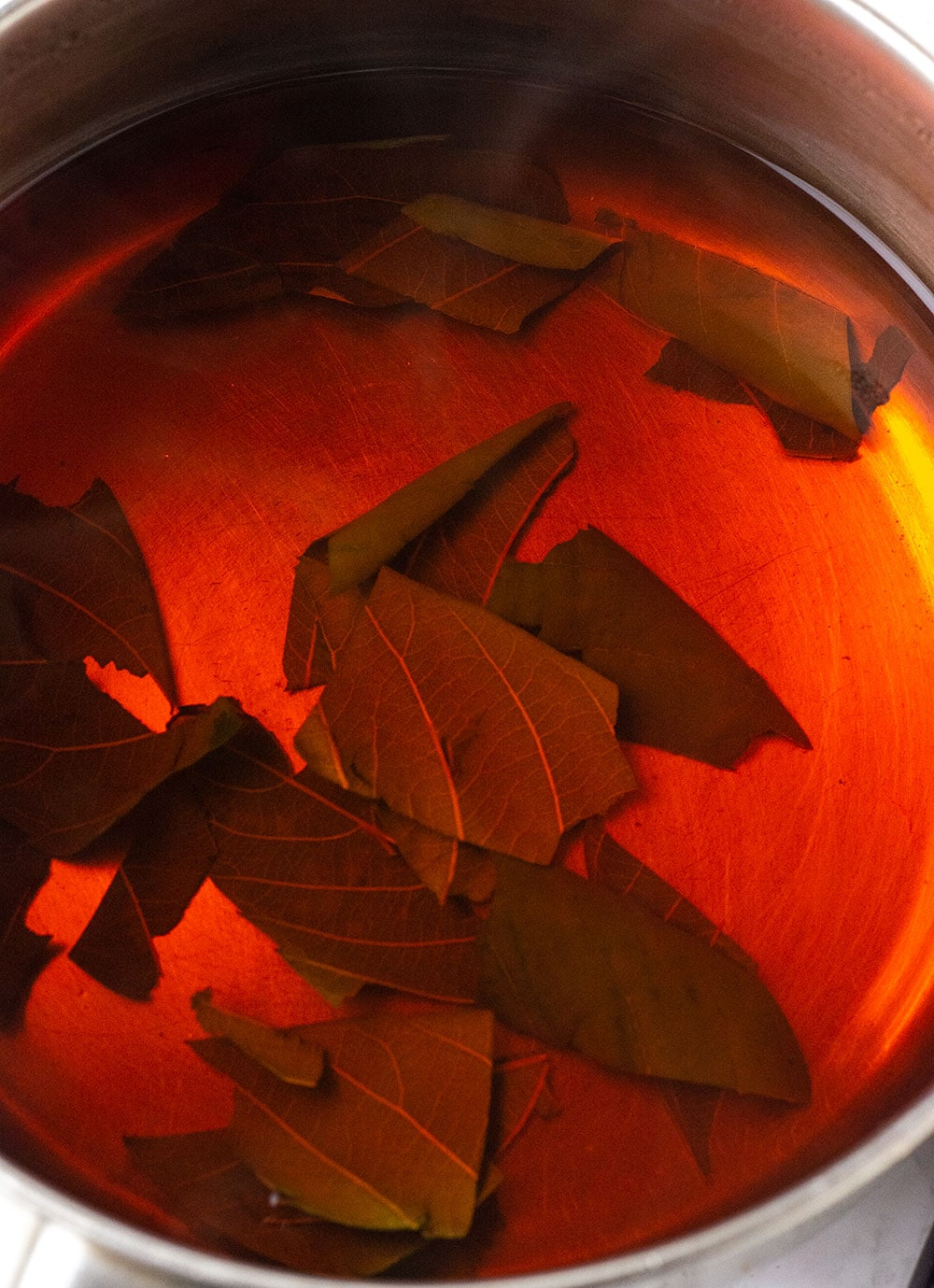 chopped loquat leaves being steeped in boiling water, water is red