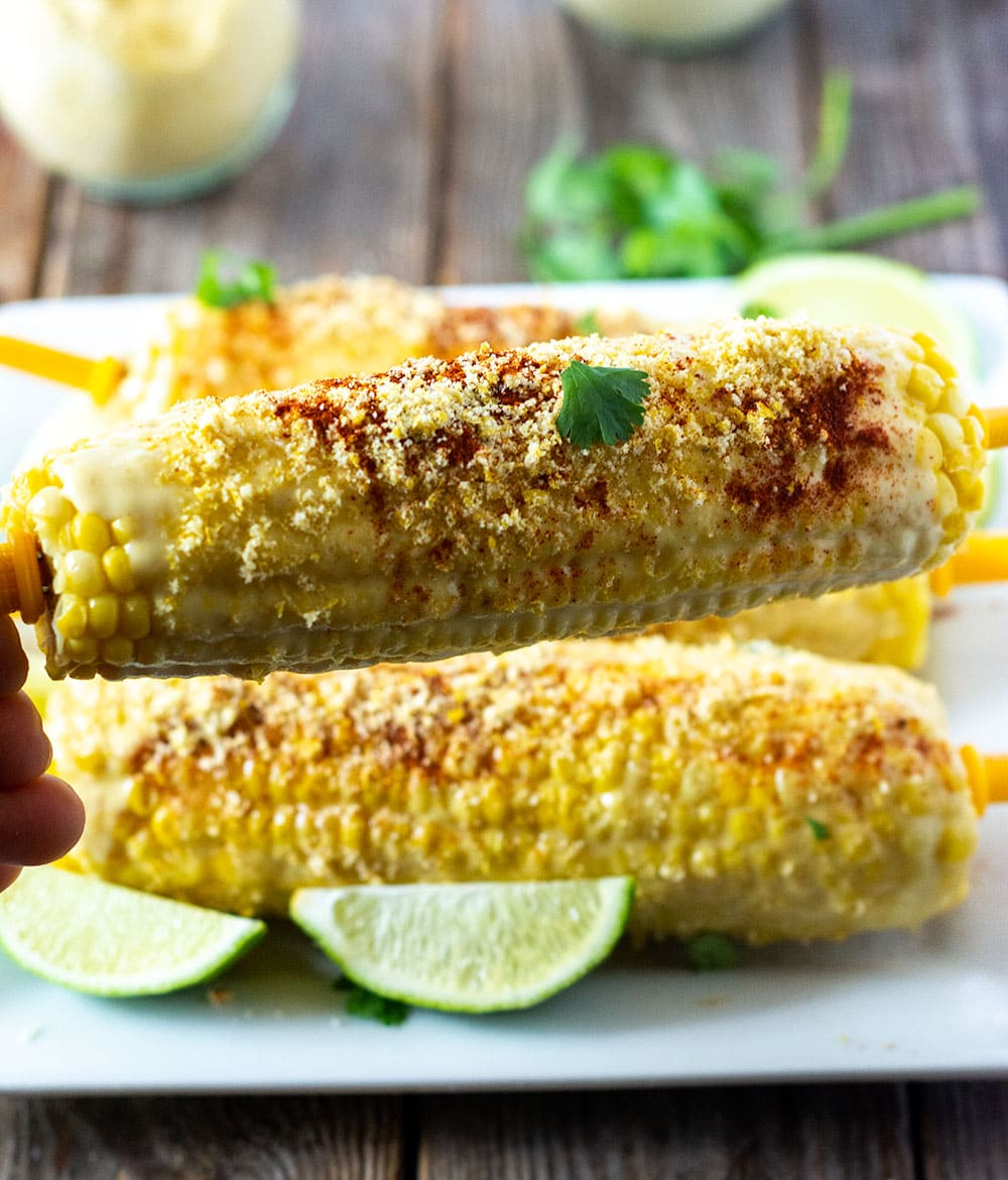 Mexican corn on a white platter, slathered with vegan mayo, vegan parmesan, cayenne pepper and lime juice