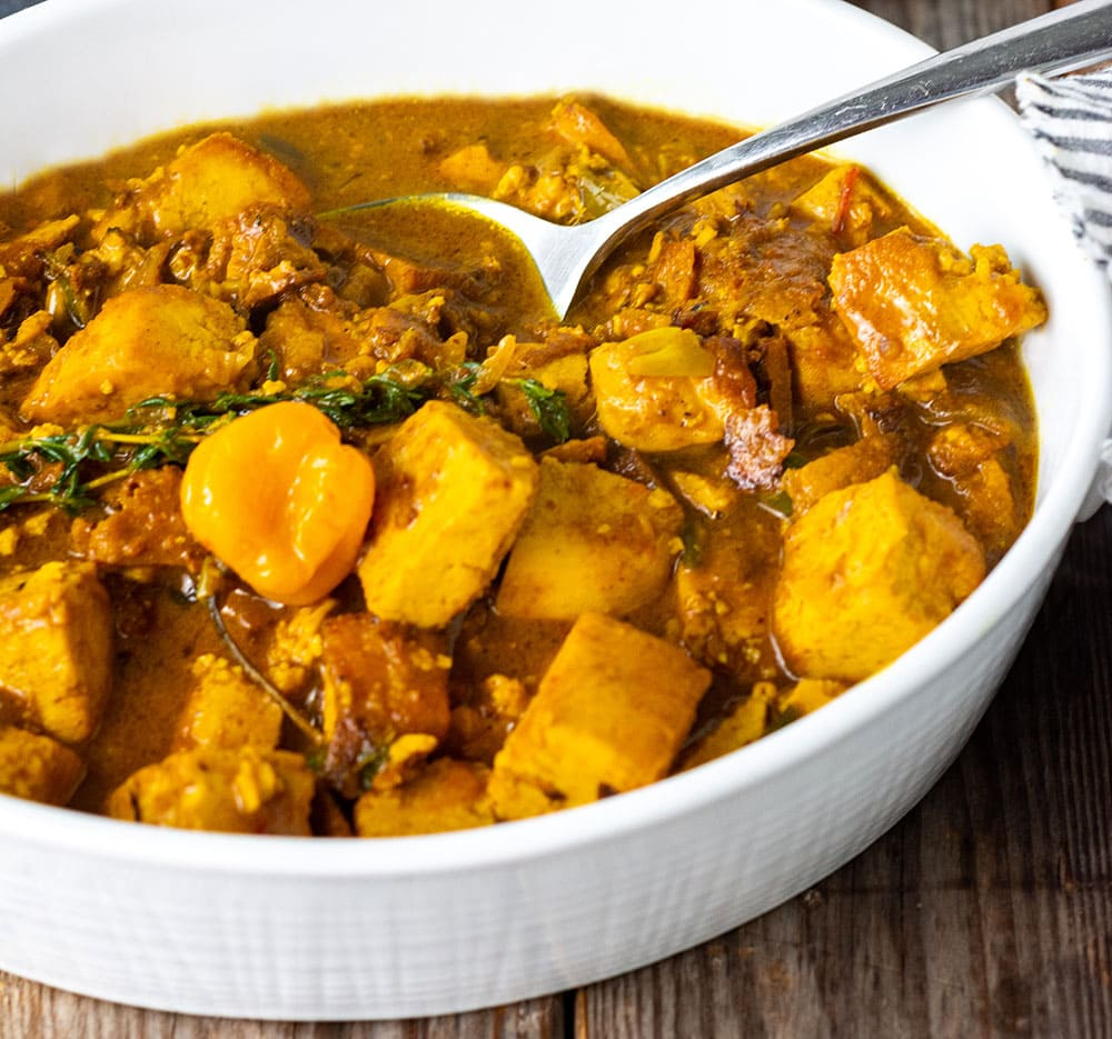 Tofu curry made with caribbean curry cooked in a seasoned coconut milk sauce with exotic herbs and spices, thyme, Scotch bonnet pepper, in a white ceramic casserole dish with a silver spoon, garnished with fresh thyme on a wooden background with a thyme sprigs on a charcoal slate in the background