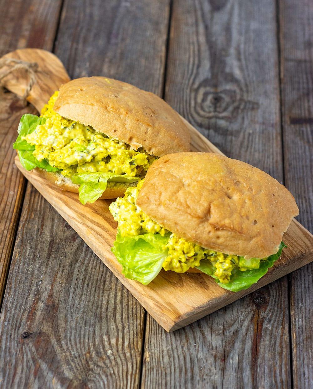 vegan tofu egg sandwiches on a cutting board with tofu scramble, mayo, lettuce