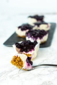 vegan blueberry cheesecake with blueberry topping, foreground with silver spoon holding cheesecake, background with mini cheesecakes on a black slate