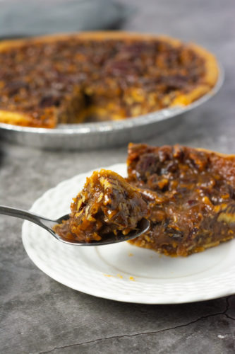 vegan pecan pie slice on a white plate with a silver spoon on a grey background