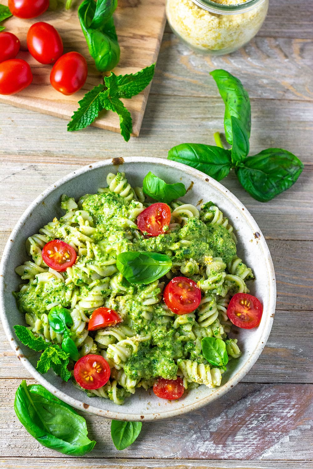 Overlay vegan pesto pasta, in a ream bowl on a wooden background with grape tomatoes, basil and mint leaves on a wooden cutting board