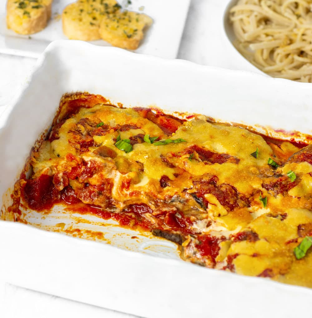 vegan parmesan recipe in white casserole dish overlay garnished with chopped basil leaves