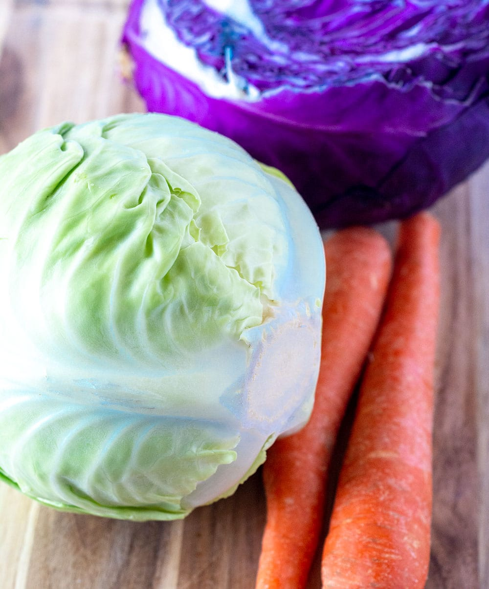 Ingredients for coleslaw, carrot, green cabbage, red cabbage on a wooden cutting board