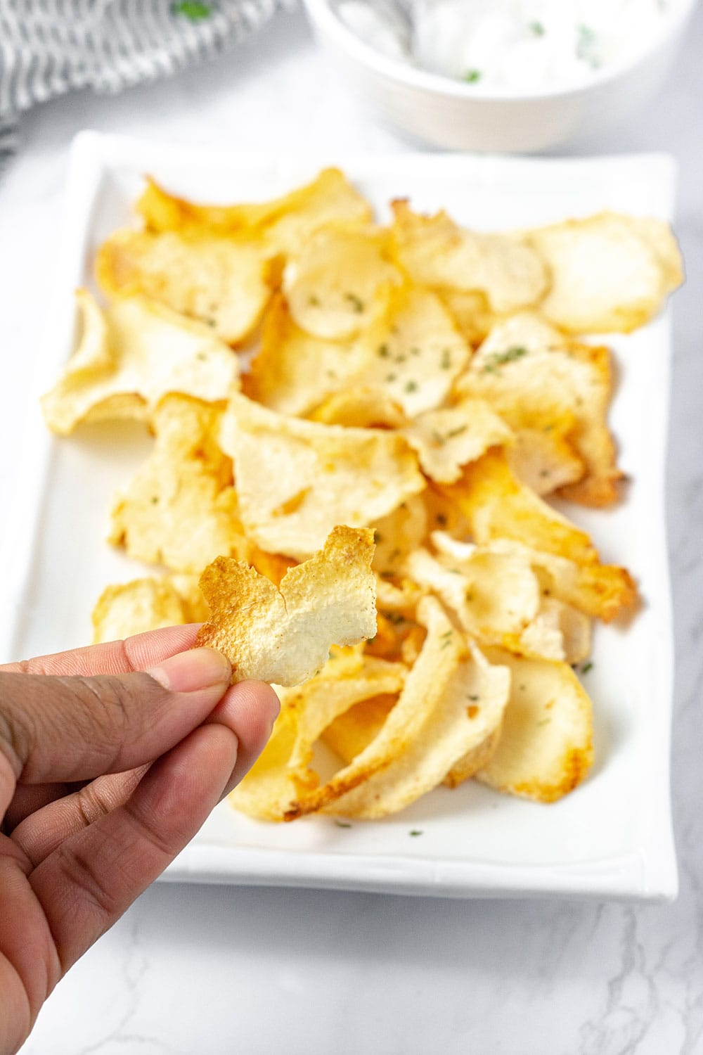 holding crispy jicama chips over a platter of chips on a white plate