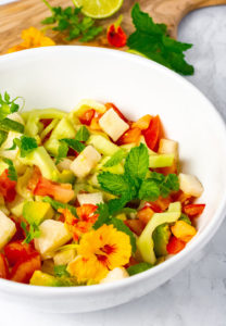 Jicama salad in a bowl with cubed jicama, tomato, cucumber, avocado tossed with lime dressing and garnish with mint, nasturtium and cilantro