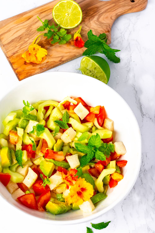 Jicama cucumber, tomato salad in a white bowl overlay