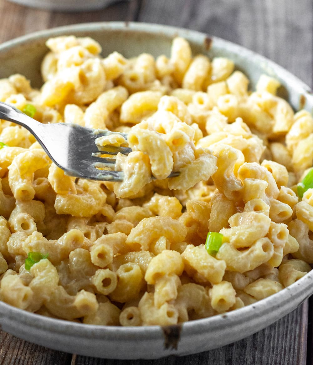 Vegan Mac And Cheese without nuts in a beige bowl with a silver fork