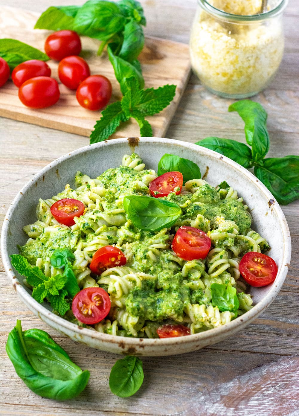 Easy vegan pesto pasta, in a ream bowl on a wooden background with grape tomatoes, basil and mint leaves on a wooden cutting board