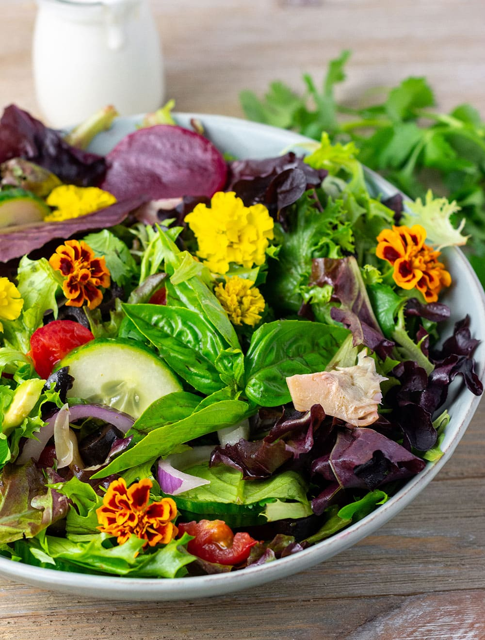 This delicious spring mix salad recipe is fresh vibrant and healthy, made with baby spring mix greens, edible flowers, tomato, avocado, cucumber, beet, artichoke hearts, red onion, olive and served with homemade salad dressing.