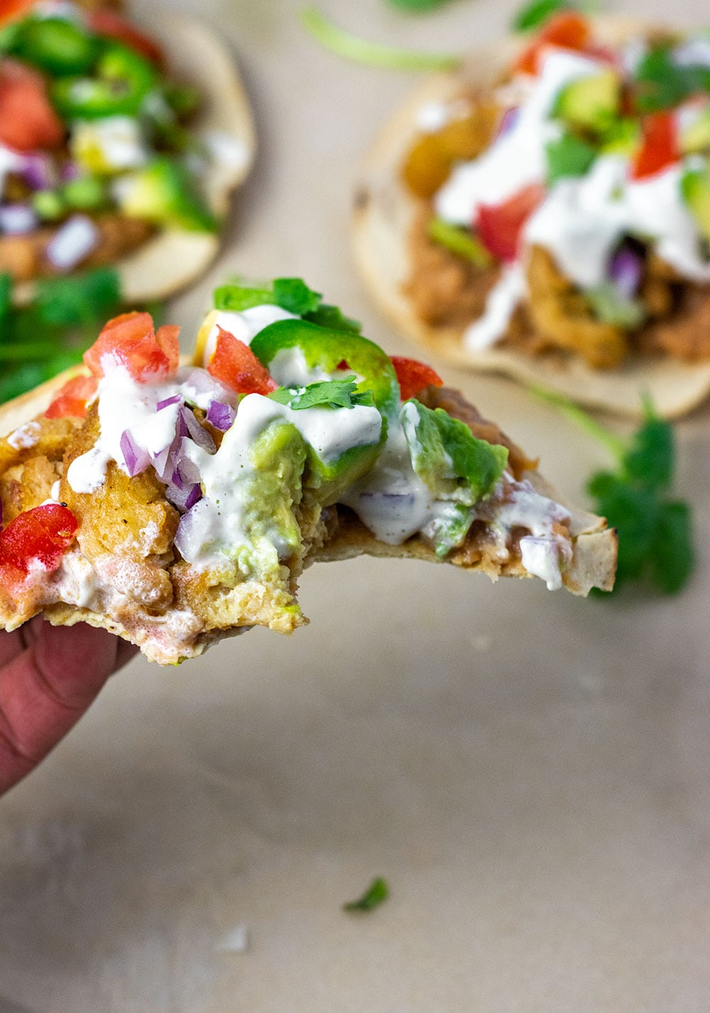 Vegan tostada recipe with refried beans, soy curls, avocado tomato, jalapeno, lettuce, cilantro. Photo showing a bite take from a tostada