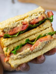 vegan tuna salad sandwich stacked in hand