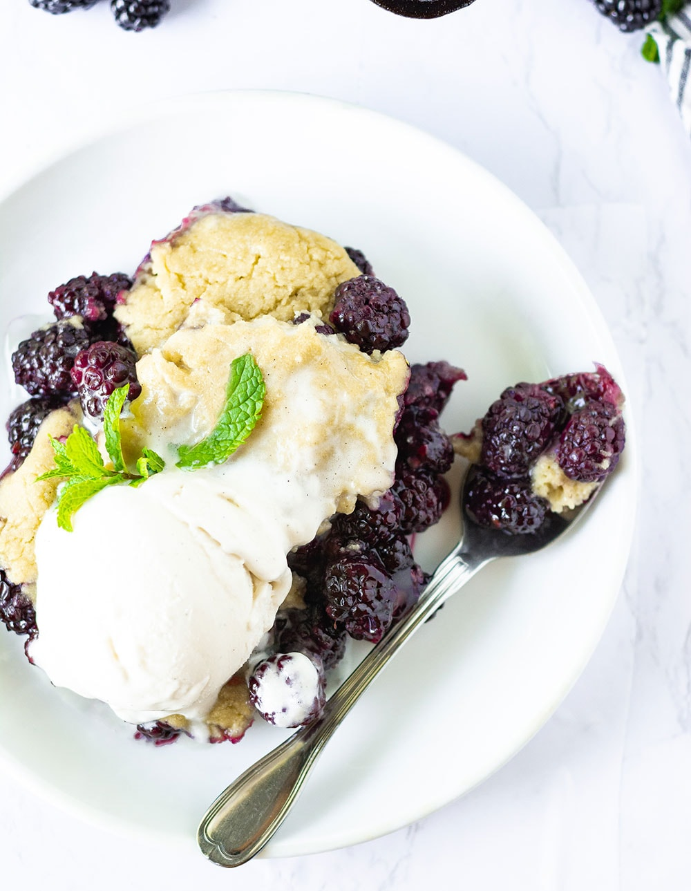 overlay vegan blackberry cobbler on a white plate with a scoop of vegan vanilla ice cream and mint leaf garnish with a silver spoon with cobbler on a white background