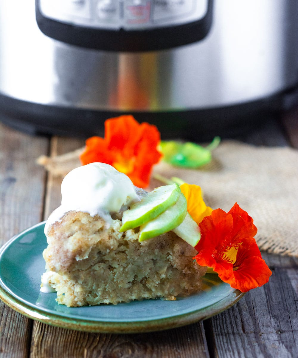 Slice of instant pot apple cake on a green plate topped with vegan vanilla ice cream apple slices and nasturtium with stant pot in the background on a wooden background.