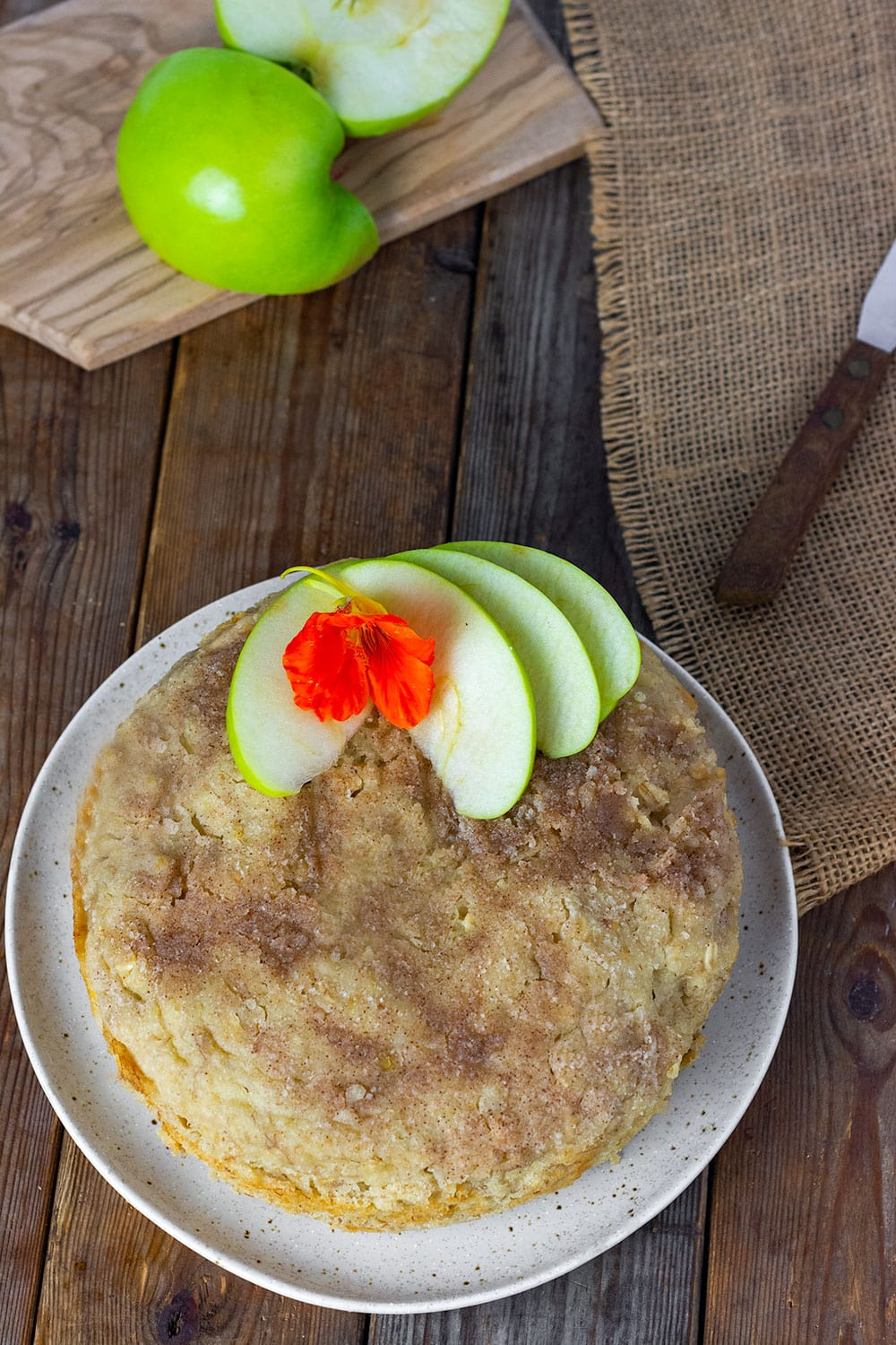 Overlay of Instant pot apple cake vegan, glutenfree, can on a beige plate with crumb topping, green apple slices and nasturtium flower with apple in the background on a cutting board
