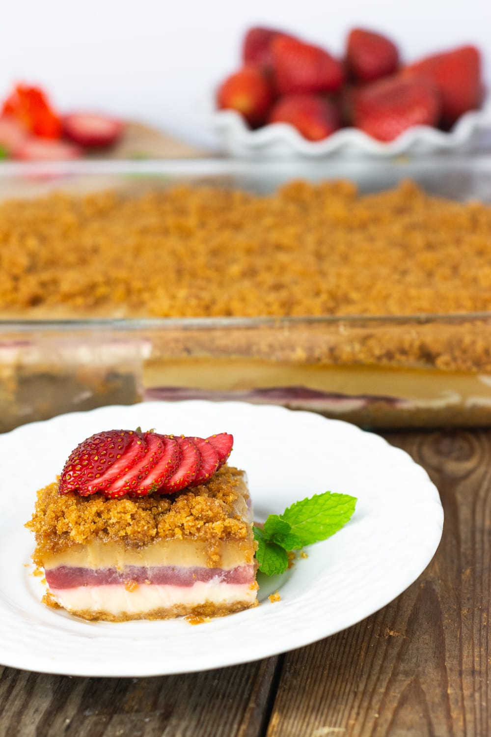 Vegan gluten-Free peanut butter lasagna garnished with strawberry slices on a white plate on a wooden board