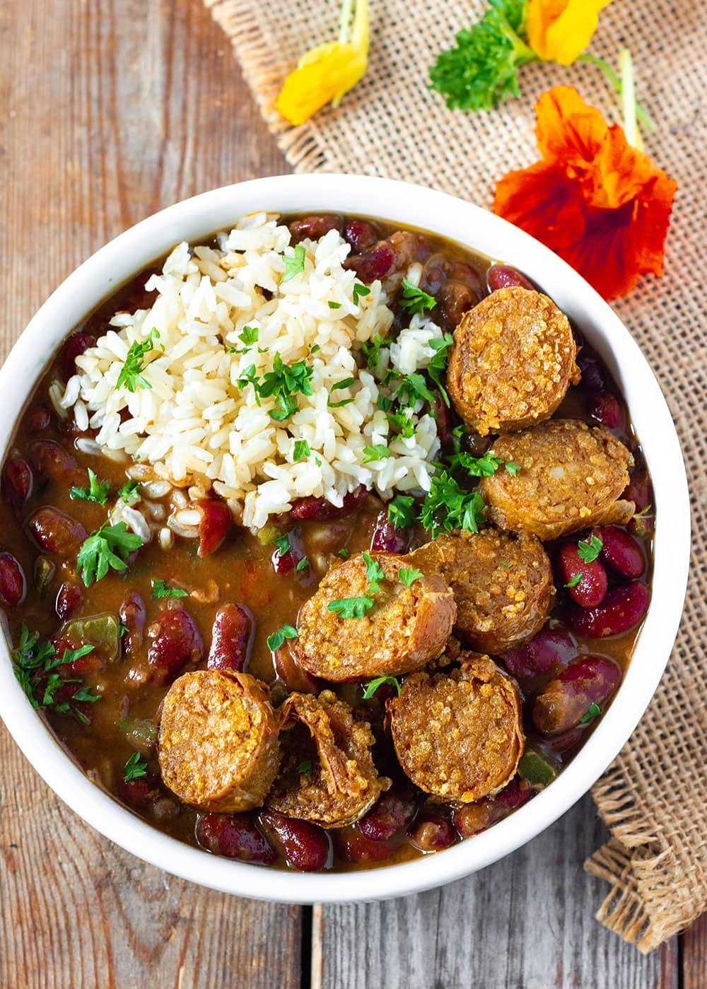 Red bean rice overlay Vegan red bean and rice in a white bowl with vegan sausage on a woo