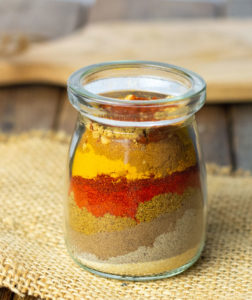 DIY Shawarma spice blend, with aromatic spices, cumin, paprika turmeric, ginger in a glass container on a burlap napkin