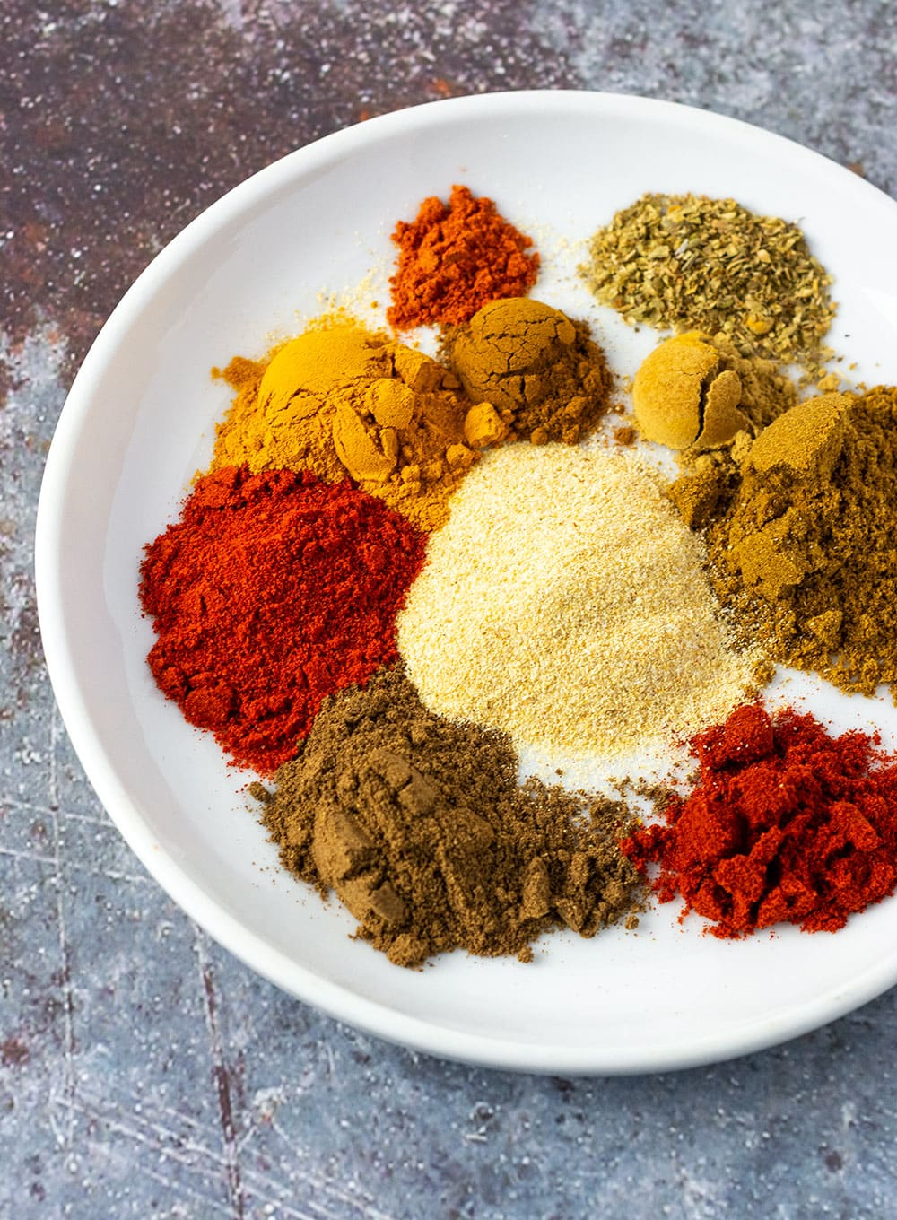 Shawarma seasoning ingredients on a white plate, paprika, cumin, allspice, turmeric, ginger, cayenne pepper, garlic powder.