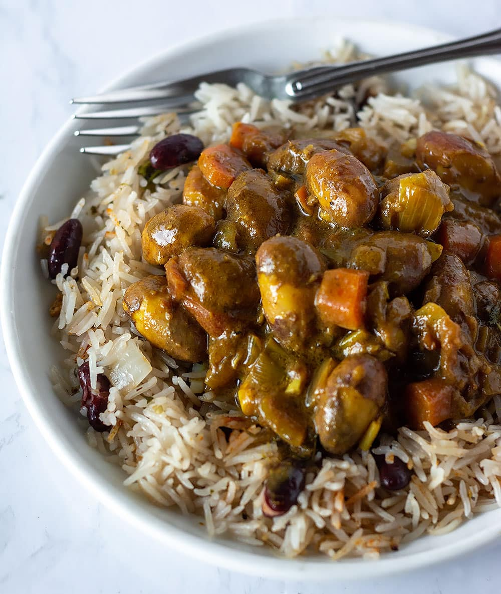 Jackfruit seed curry on a bed of rice and peas in a white plate with a fork