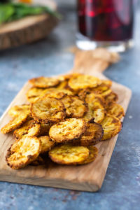Air Fryer Jerk Plantain Chips on a cutting board on a grey background
