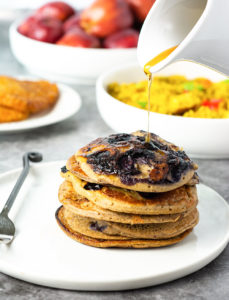 Banana Blueberry Pancakes on a white plate with a marbled background