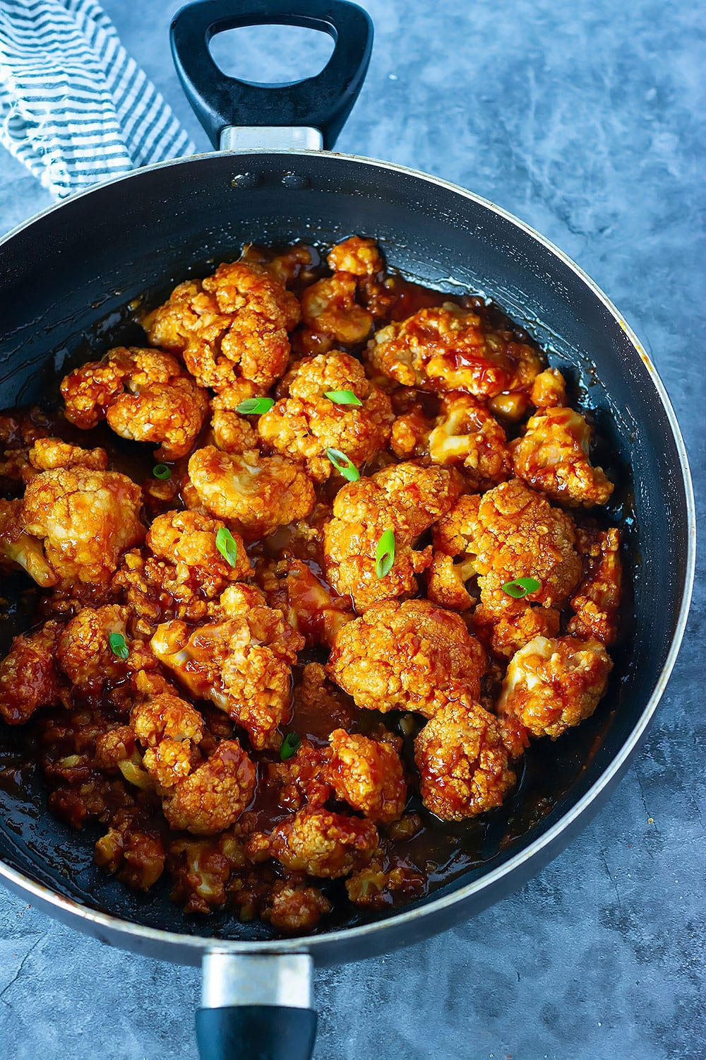 Overlay, general tso cauliflower in a black saucepan on a blue marble background