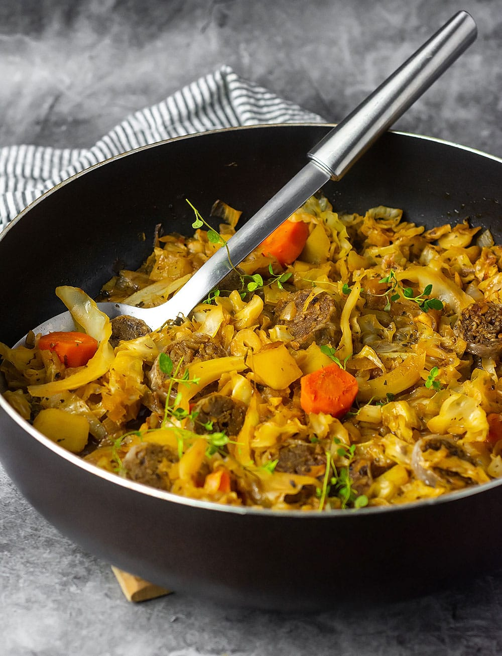 black skillet with cabbage, sausage potato, carrots.