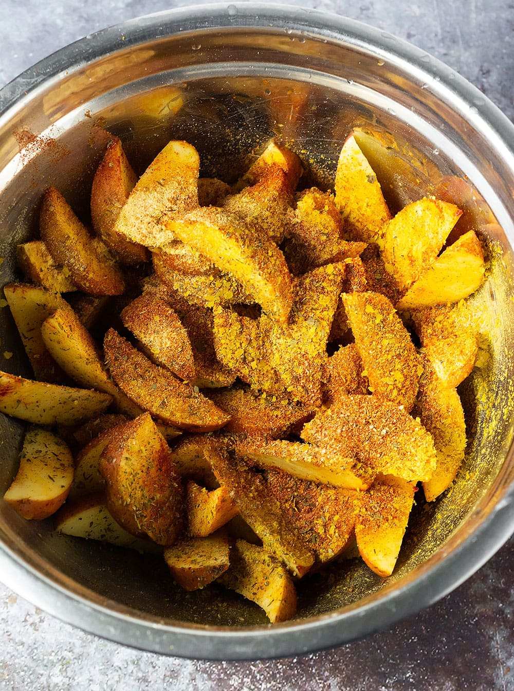 Cajun oven baked potato wedges with seasoning blend in a silver bowl