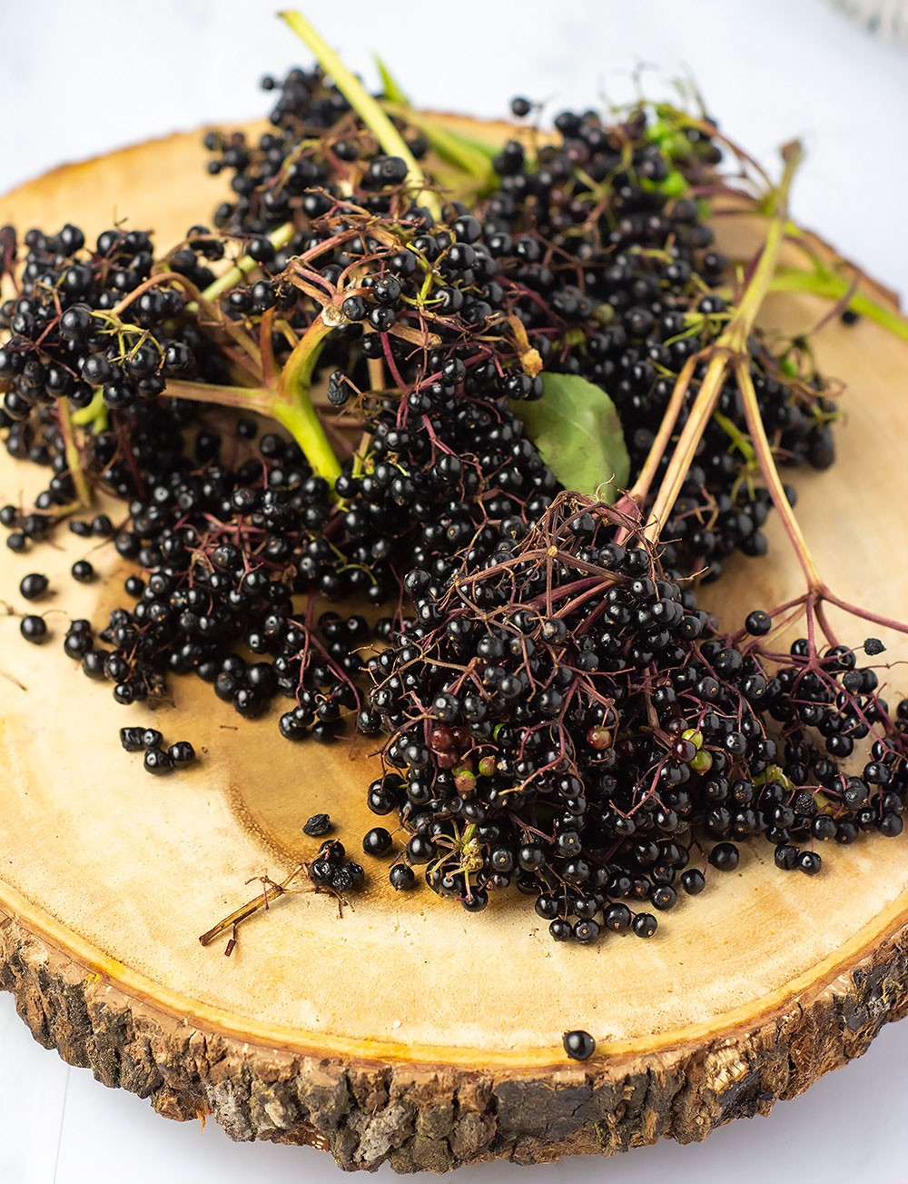 Elderberries for making elderberry syrup on a wooden cutting board with stems and leaves