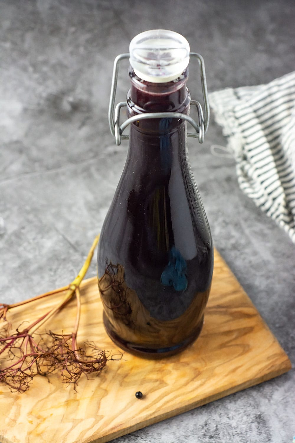 Elderberry syrup recipe in a glass jar on a wooden cutting board with a stem of elderberry on a concrete background