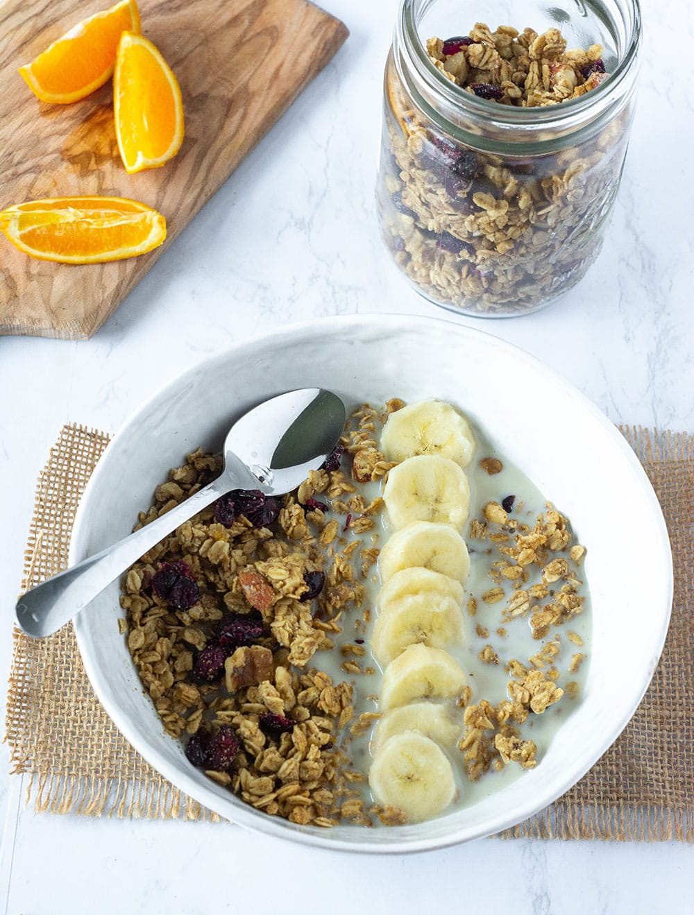 overlay gluten-free granola in a white bowl, with banana slices, orange cardamon flavor on a white marble with burlap napkin