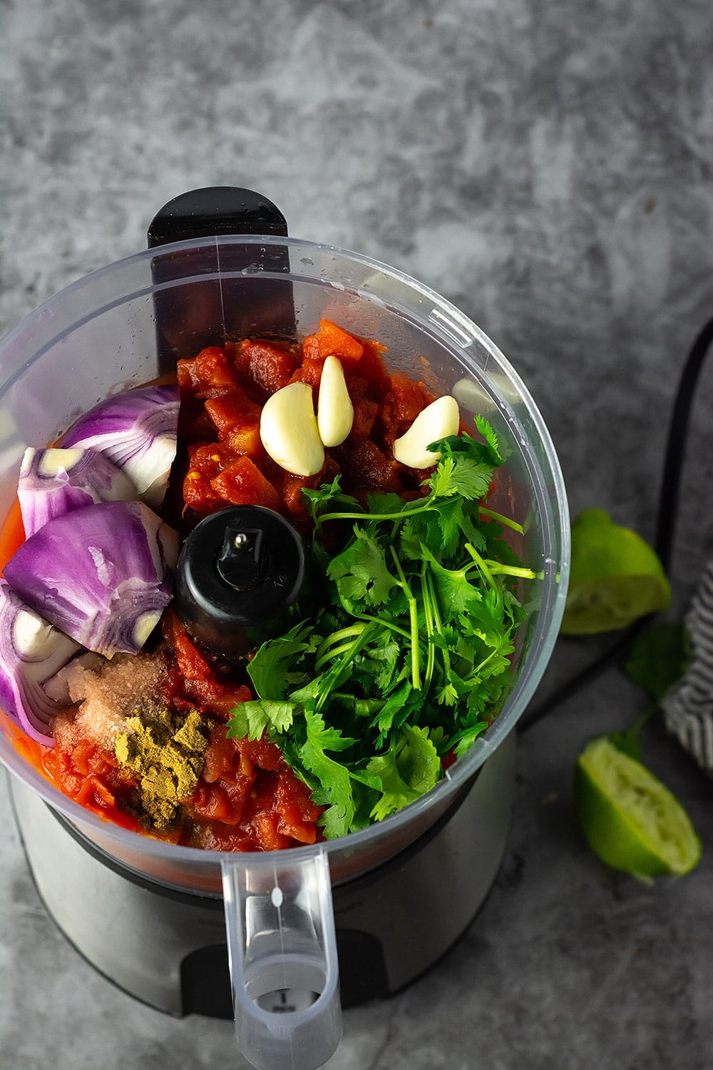 Ingredients for simple salsa in the bowl of a food processor