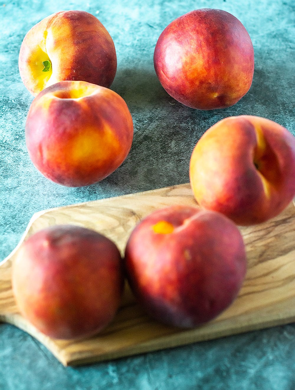 6 peaches for peach cobbler on a cutting board