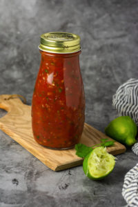 simple salsa recipe in a glass jar with a gold lid on a cutting board