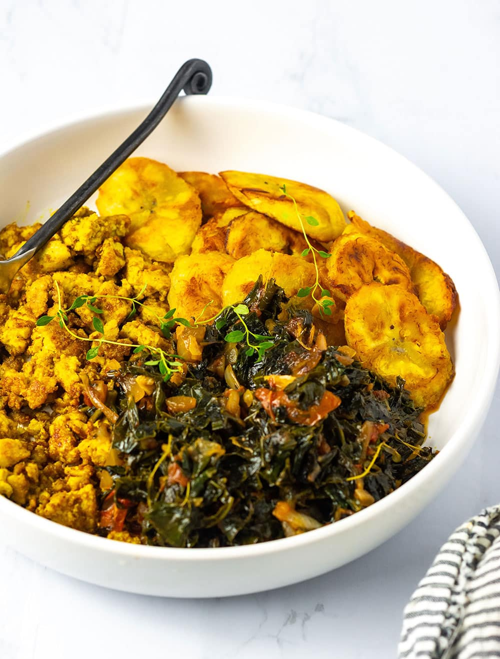 Steamed Chaya-Tree spinach in a bowl with tofu scramble, baked plantains with a fork with a black handle on a white background