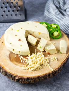 Vegan Pepper Jack Cheese on a wooden board with jalapeno garnsh