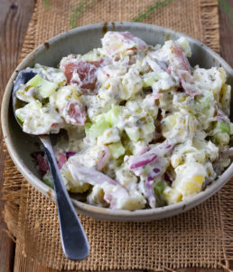 Dill potato salad in a biege speckled bowl on a wooden background