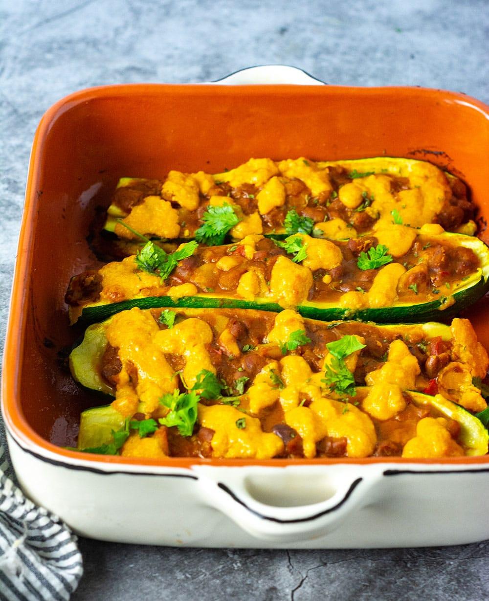 Straight on view of egan zucchini boatss in an orange casserole dish,zucchini boats stuffed with seasoned pinto beans, vegan cheese sauce